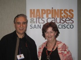 photo of David Van Nuys, Ph.D. and Beth Phelan in front of Happiness Conference sign